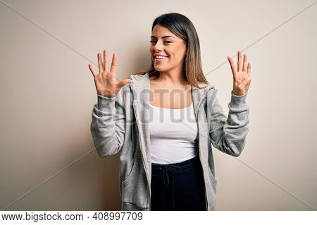 Young beautiful brunette sportswoman wearing sportswoman training over white background showing and pointing up with fingers number nine while smiling confident and happy.