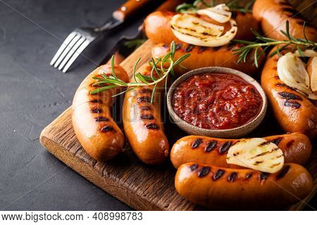 Fried Delicious Sausages With Tomato Sauce And Herbs On Cutting Board, Black Background.