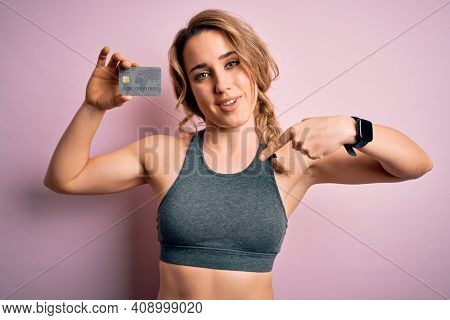 Young beautiful blonde sportswoman wearing sportswear holding credit card to payment with surprise face pointing finger to himself