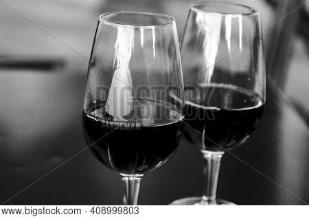 Porto, Portugal- December 30, 2019: Two Glasses Of Tasty Port Wine Tawny Sandeman Brand On A Table I