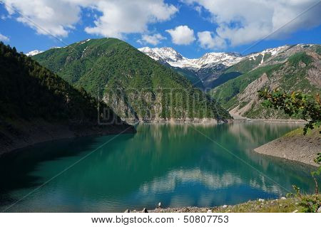 Charming lake among high picturesque mountains and a cloud in the blue sky