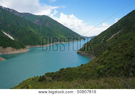 Long lake among high charming mountains and blue sky