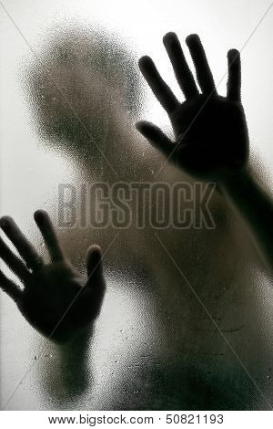 Silhouette Of A Man With Hands On A Frosted Glass