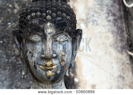 Head detail of old Buddha statue in the Wat Saphan Hin temple in Sukhothai historic park, Thailand