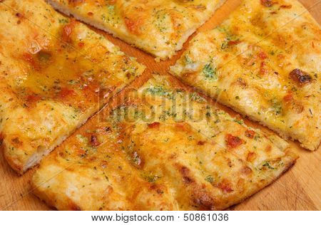 Garlic pizza bread with sunblush tomatoes and herbs.