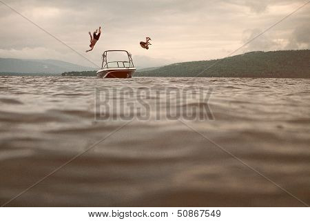 Two Young Man Jumping Of A Boat