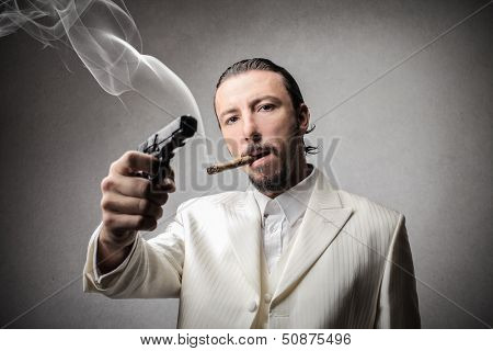 mafia man with a cigar in mouth and a gun in hand