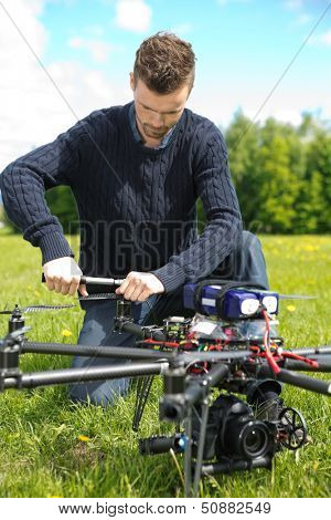 Young technician assembling propeller of UAV octocopter in park
