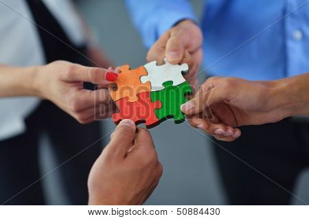 Group of business people assembling jigsaw puzzle and represent team support and help concept
