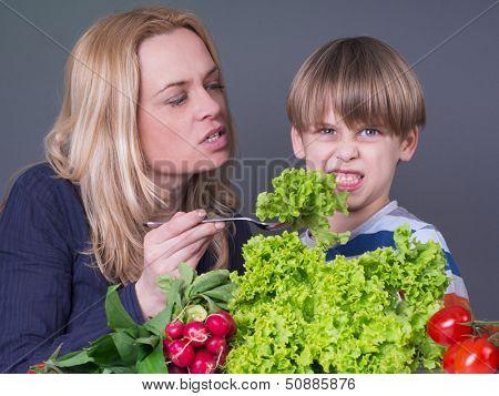 Little boy  refusing to eat green salad
