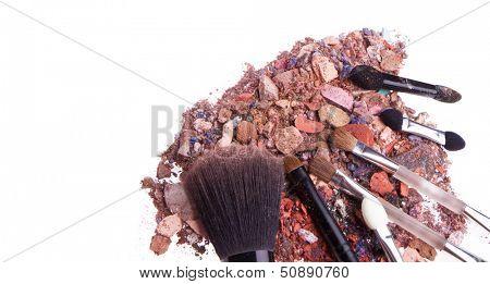 crushed eyeshadows with set of brushes isolated on white background