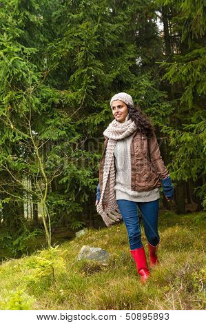 Woman walking in pinewood autumn wear knitted scarf and hat