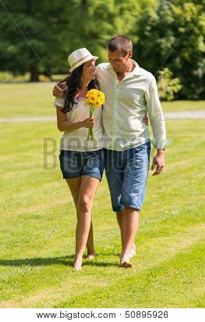 Happy young couple walking in park barefoot