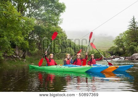 Friends kayaking together cheering at camera in a lake in countryside