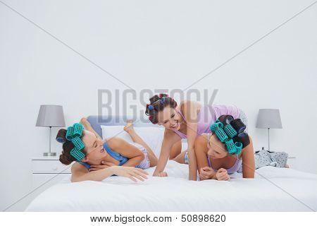 Girls in hair rollers having fun in bed at sleepover