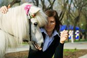Young woman with a her loved white pony. poster