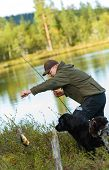 Fisherman get a perch with rod and reel vertical image poster