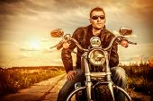 Biker man wearing a leather jacket and sunglasses sitting on his motorcycle looking at the sunset. poster
