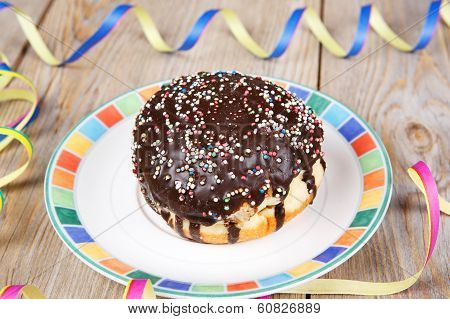 Chocolate donut with carnival decoration. German traditional kreppel for carnival poster