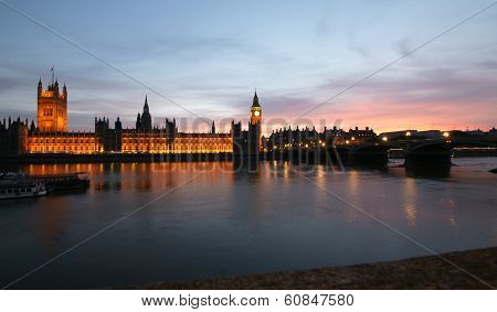 A View Across The River Thames Of The Houses Of Parliament At Sunset.