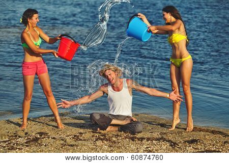 Friends with plastic containers splashing water over one another's heads at the beach