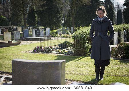 Woman looking at gravestone
