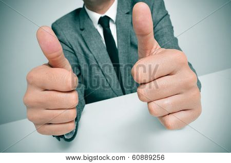 man wearing a suit sitting in a desk giving a thumbs up signal with both hands