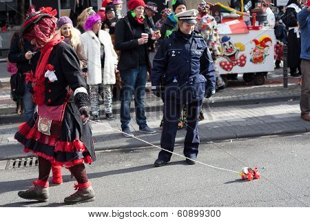Female Police Officer Looking At A Toy On A Carnival Procession
