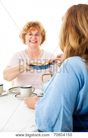 Two mature ladies having a tea party together.  White background