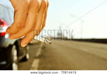 closeup of a man with a burning cigarette in his hand while is waiting besides a car parked next to a no traffic road