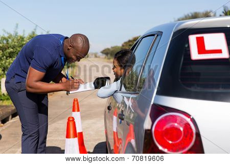 male african driving instructor and student driver in testing ground
