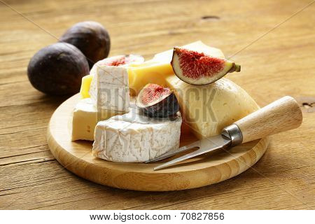 cheeseboard with maasdam, camembert, cheddar cheese and figs