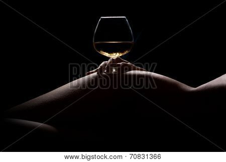 Beautiful, nude woman body silhouette and a glass of alchohol