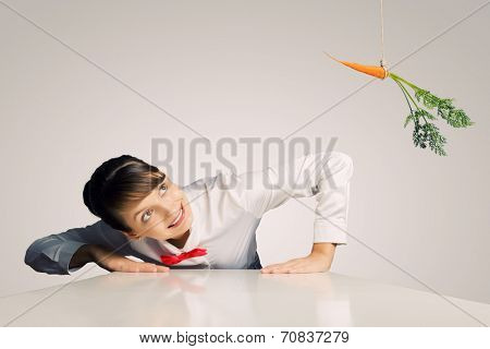 Funny image of businesswoman chased with carrot