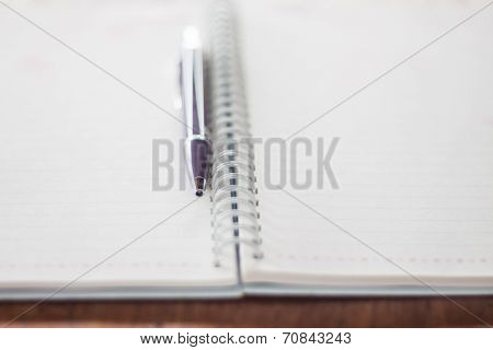 Pen And Spiral Notebook On Wooden Table