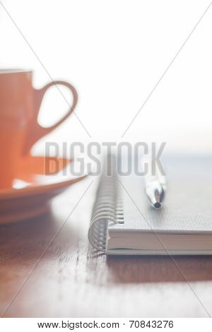 Orange Coffee Cup, Pen And Notebook On Wooden Table