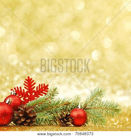 Christmas card with fir branch and decorations on golden gitter background