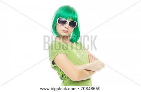 Girl with an attitude in an iridescent green wig and sunglasses standing glaring at the camera with folded arms, on white with copyspace