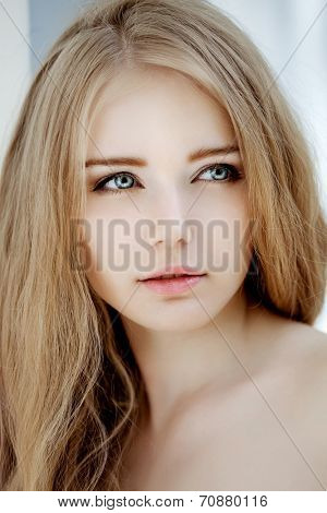 Woman face close up. A pretty young blond trendy. Girl with a beauty face. Beautiful female face with luxury make-up  poster
