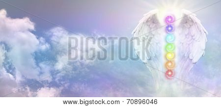 Wide blue sky banner with fluffy clouds and a pair of white Angel Wings with the Seven Chakras between the wings and a bright sunburst behind the uppermost chakra poster
