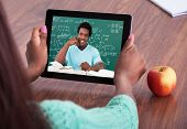 Cropped image of female teacher assisting student through video conferencing at classroom poster