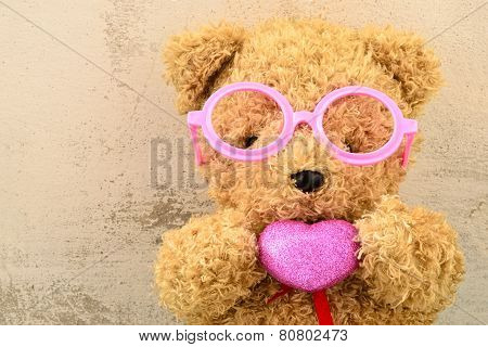 love ly bear doll wearing pink glasses and holding pink heart shape poster