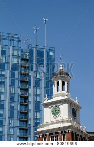 Wind turbines on modern building contrasting with old building