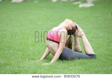 Young woman practicing yoga eka pada Rajakapotasana (King Pigeon Pose) pose on lawn poster