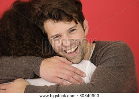 Man and woman hugging on red background