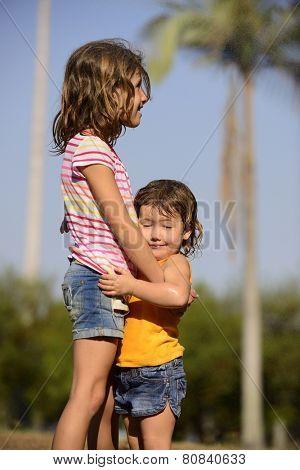 Children having fun in tropical summer rain