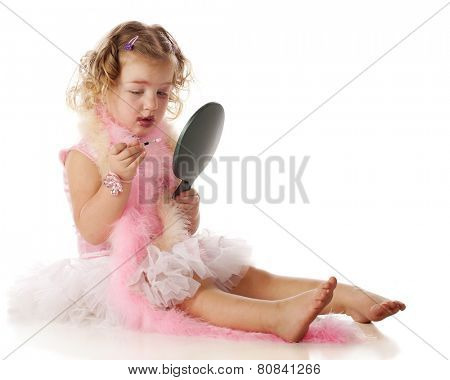 A beautiful little girl in boas and a petticoat, applying her mom's makeup on herself.  She appears to be wondering what to do with a little eye-liner brush.