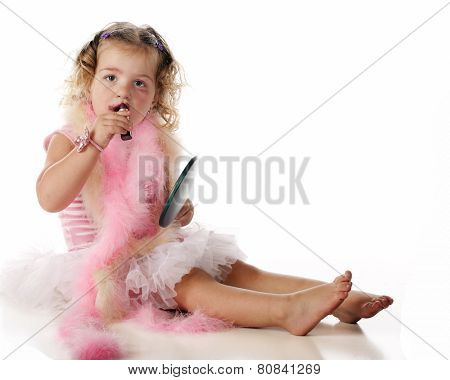 An adorable preschool girl applying makeup while dressed in boas and a petticoat.  Isolated on white.