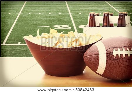 Chips, football and Six Pack of Beer on a table in front of a big screen TV with a Football field. Great for Super Bowl themed projects. Horizontal format with instagram effect applied.