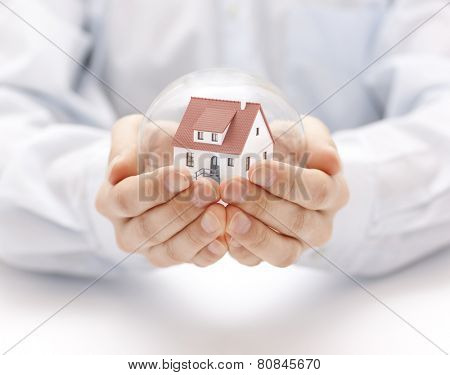Crystal ball with house in hands